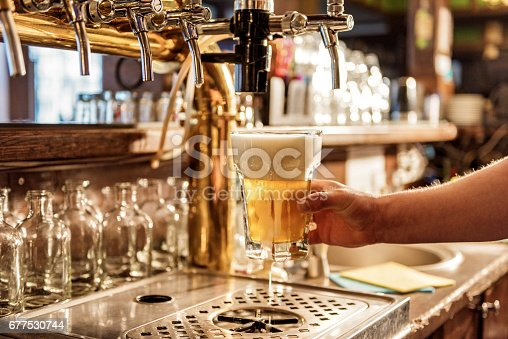 istock Male arm keeping pouring beer in alehouse 677530744
