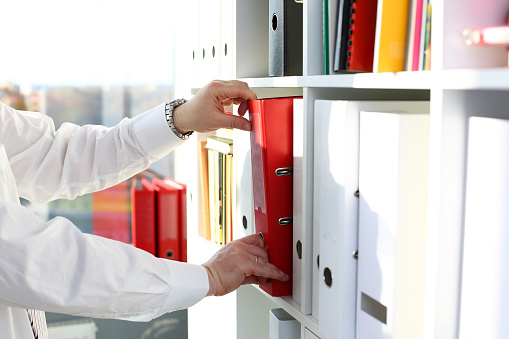 Male arms pick red file folder from office book shelf