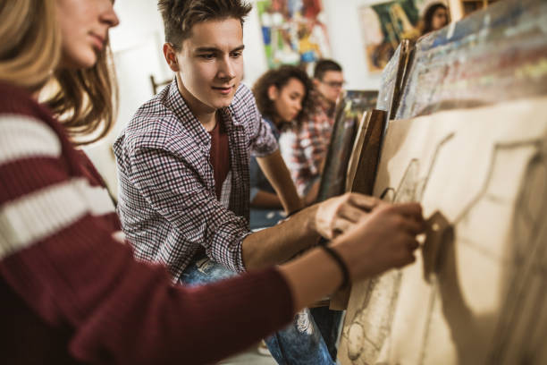 männliche kunststudentin unterstützung seiner freundin während einer klasse im art studio. - high school bilder stock-fotos und bilder