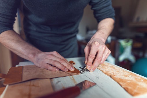 istock Male artisan making leather case in his atelier 1150935067