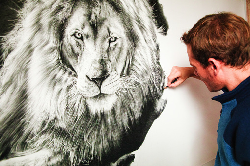 Over the shoulder view of a male artist drawing a lion with a charcoal pencil. The paper canvas is hanging on a wall.