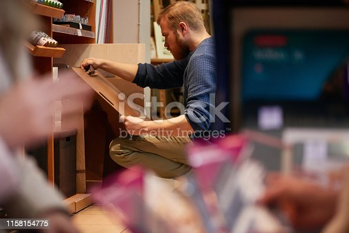 Side view of handsome bearded man in casual outfit looking at portable drawing board while sitting on haunches near shelves in art store