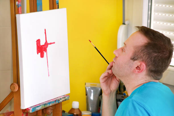 Pintor masculino do artista que trabalha na oficina com a lona no cavalete de madeira da placa de desenho no estúdio da pintura da arte. O retrato do artista com pincel está pintando na lona com pinturas de petróleo. Conceito da faculdade criadora. - foto de acervo