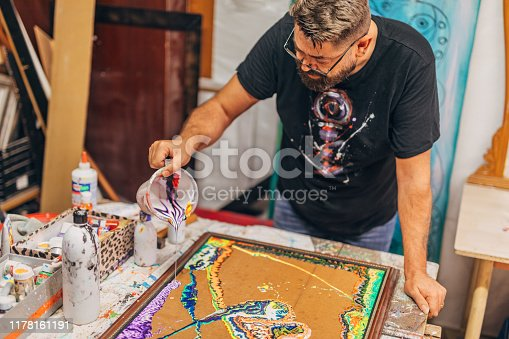 Male artist in his studio, pouring acrylic colors on canvas.