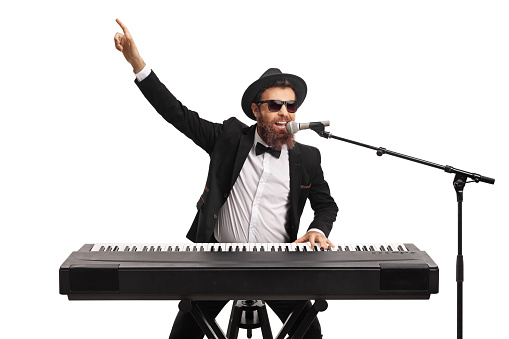 Male artist playing a keyboard and pointing with hand isolated on white background