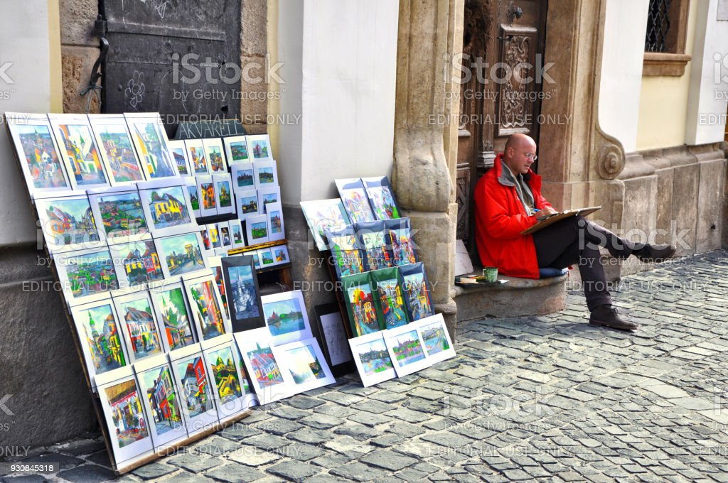Male artist sales his paintings on the streets. stock photo