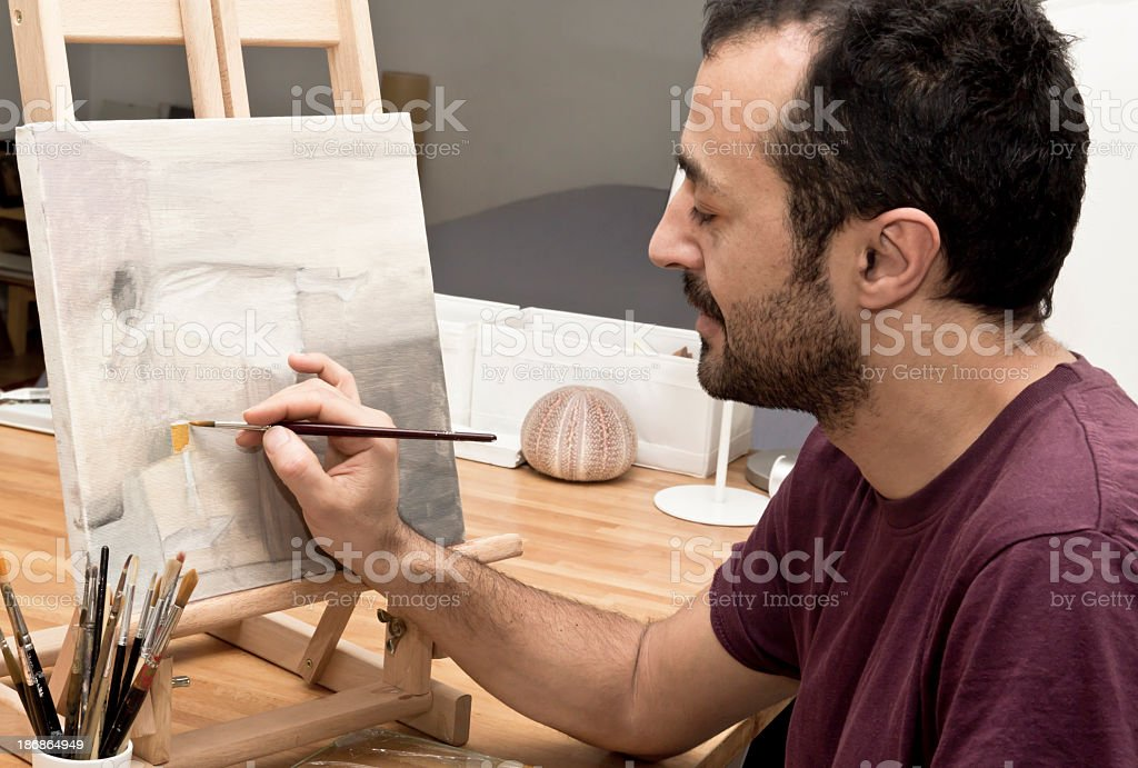 Male artist working on abstract painting on small easel stock photo