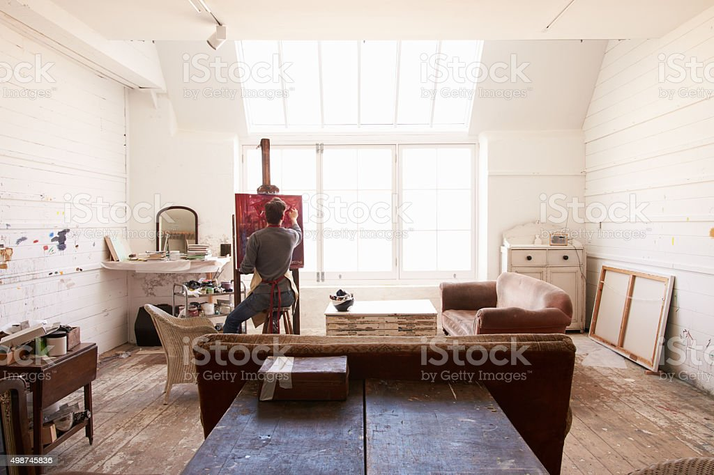 Male Artist Working On Painting In Bright Daylight Studio stock photo
