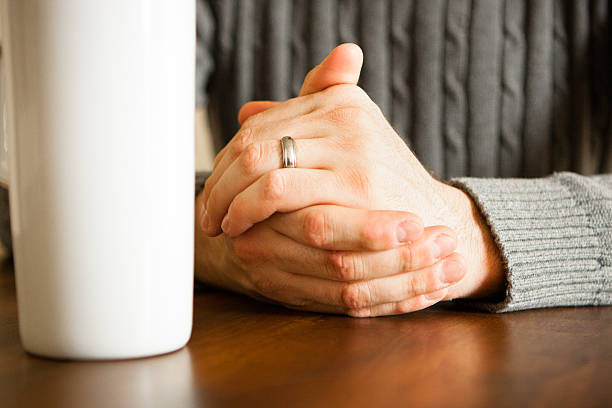 Male at Table, Hands folded with coffee mug stock photo
