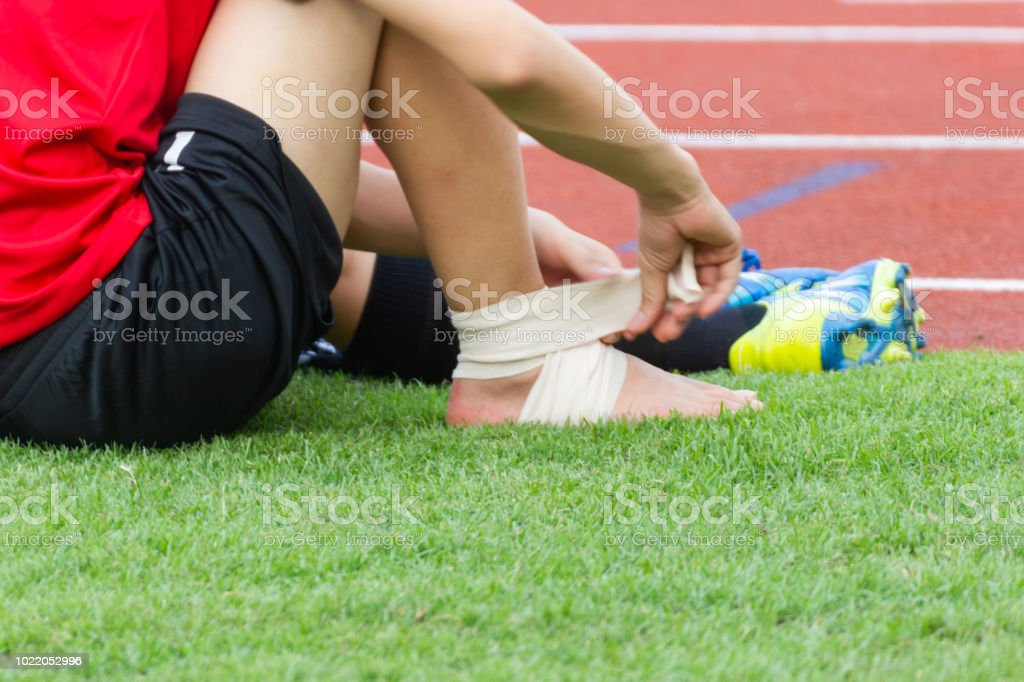 Male athlete applying compression bandage onto ankle injury of a...