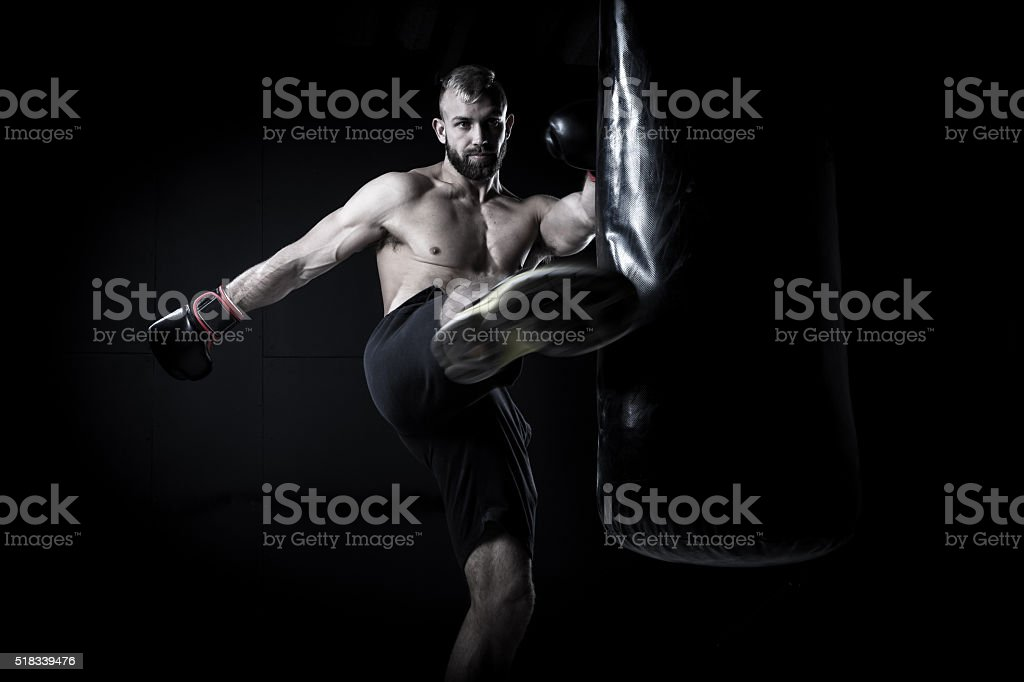 Male Athlete boxer punching a punching bag stock photo