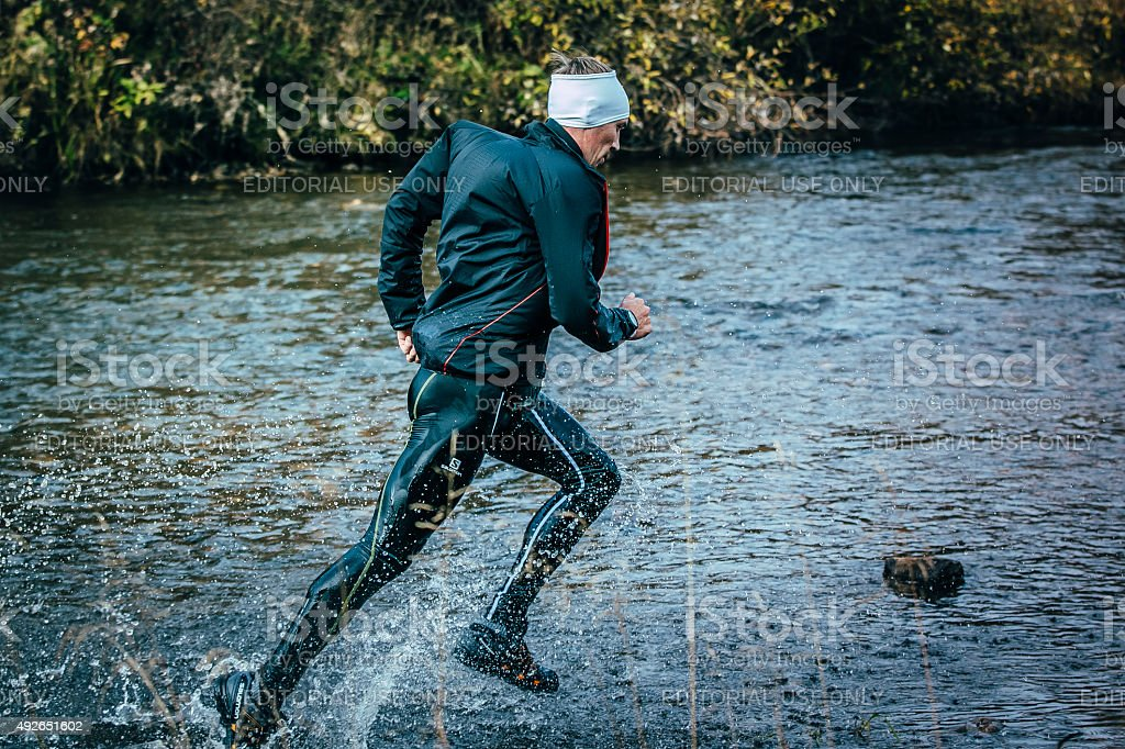 male athlete crossing the river on rocks side view stock photo