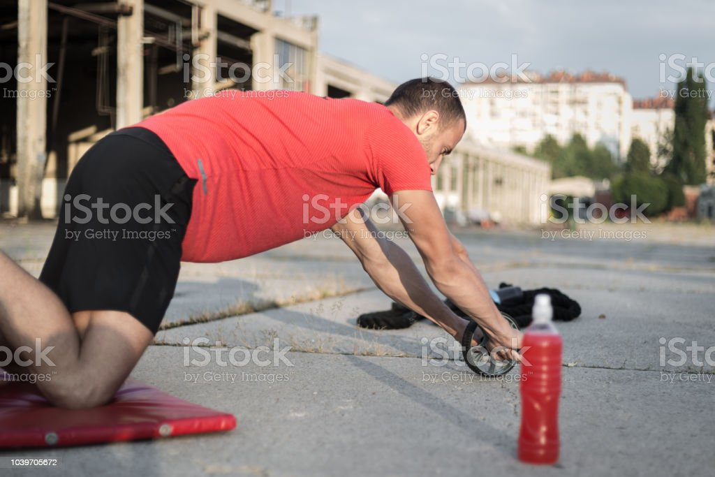 Male athlete doing abs on rolling wheel stock photo