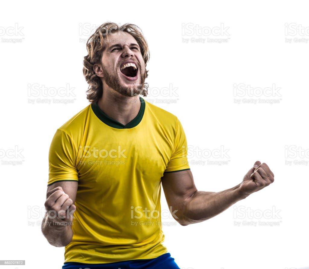 Atleta masculino / ventilador de uniforme amarelo, comemorando em fundo branco - foto de acervo