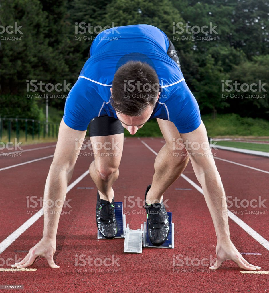 Male athlete getting ready on a starting block stock photo