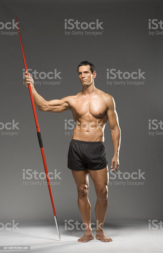 Male athlete holding javelin, studio shot royalty free stockfoto