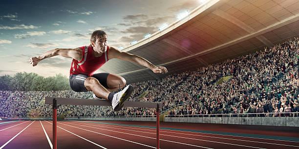 Male athlete hurdling on sports race stock photo