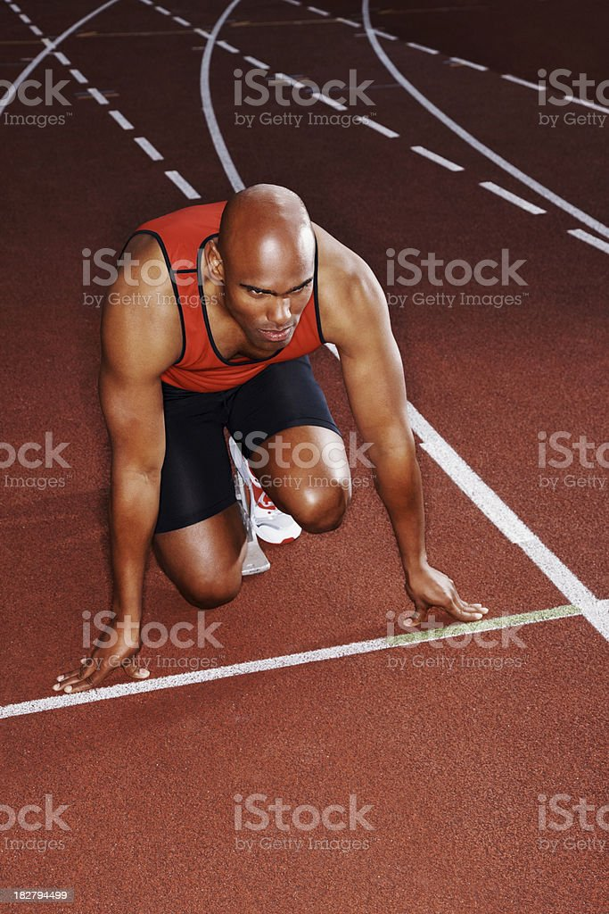 Male athlete in start position on a running track royalty-free stock photo