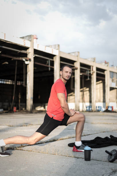 Male athlete is stretching after workout stock photo