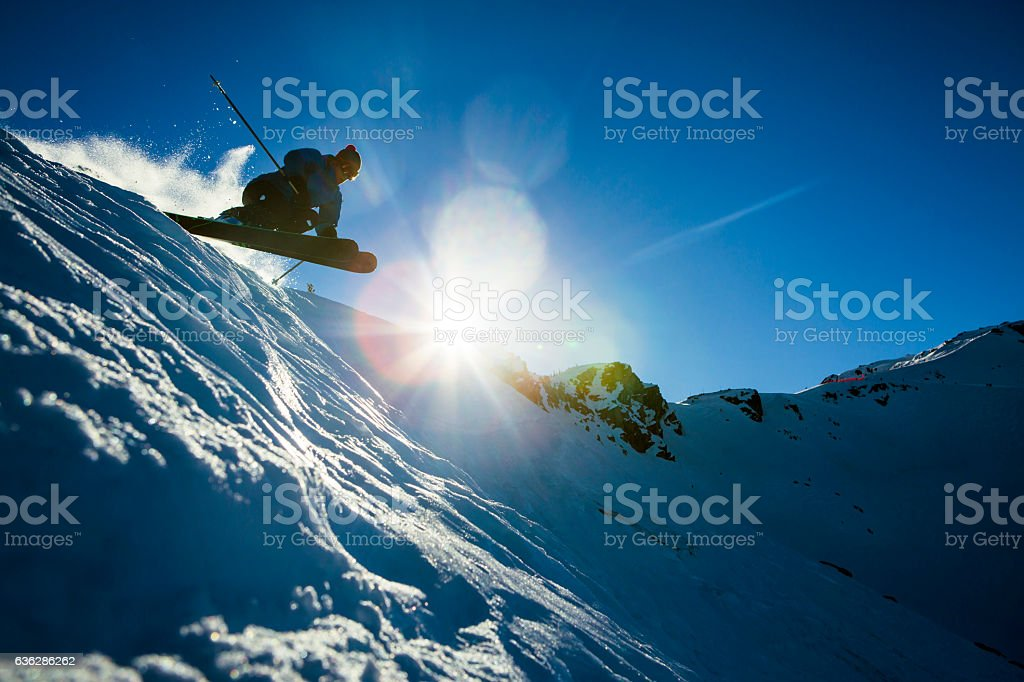 Male athlete jumping on skis. stock photo