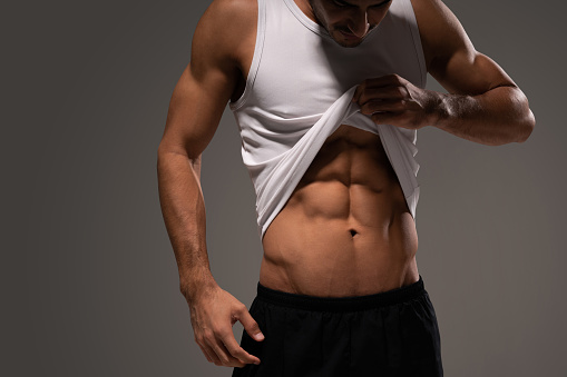 Latin fit young man showing ripped abs while standing in studio