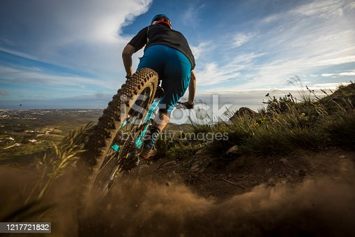 Fit man riding his mountain bike on trail in Portugal.