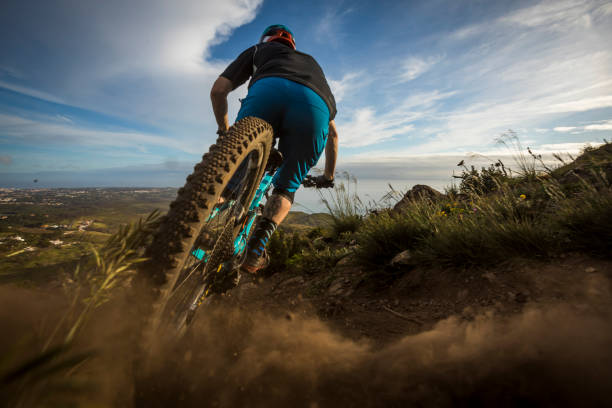 Male athlete mountain biking in Portugal. Fit man riding his mountain bike on trail in Portugal. mountain biking stock pictures, royalty-free photos & images