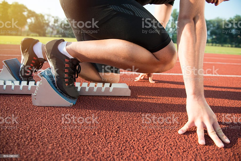 Male athlete on starting position at athletics running track. stock photo