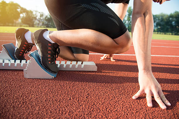 Male athlete on starting position at athletics running track. Male athlete on starting position at athletics running track. Runner practicing his sprint start in athletics stadium racetrack. track starting block stock pictures, royalty-free photos & images