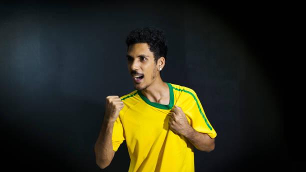 Atleta masculino ou fã de uniforme amarelo, comemorando em fundo preto - foto de acervo
