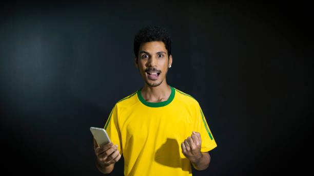 Atleta masculino ou fã em amarelo uniforme olhando celular em fundo preto - foto de acervo