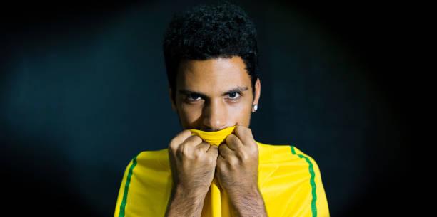 Atleta masculino ou fã beijando uniforme amarelo sobre fundo preto - foto de acervo