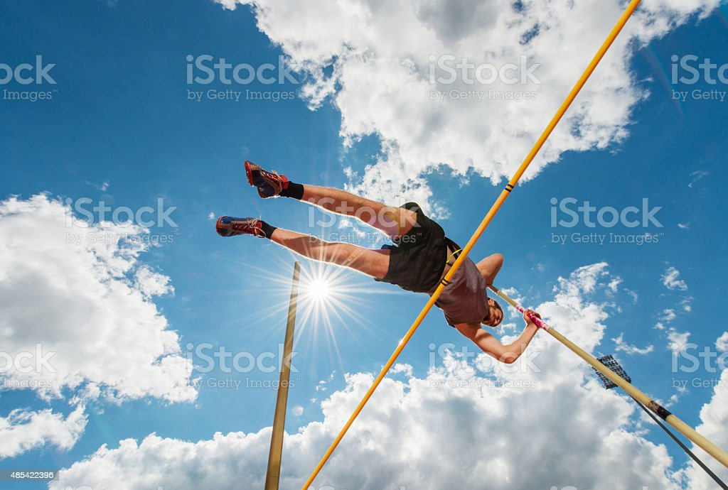 Male athlete performing high jump against the sky. stock photo