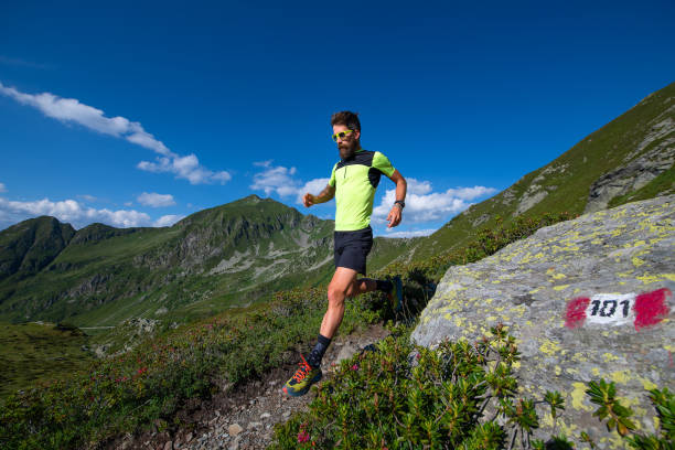 male athlete practicing mountain running on a trail downhill - carpet runner stock photos and pictures