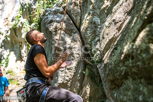 Caucasian male athlete prepared for climbing on the rock mountain.