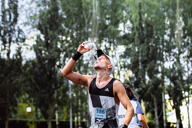 male athlete runner hot weather pouring water on head stock photo