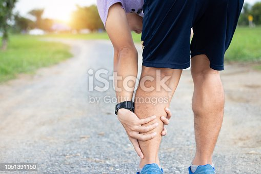 istock Male athlete runner muscle and ankle injury after jogging. Athlete man runner touching muscle in painful. Muscle and ankle injury concept. 1051391150