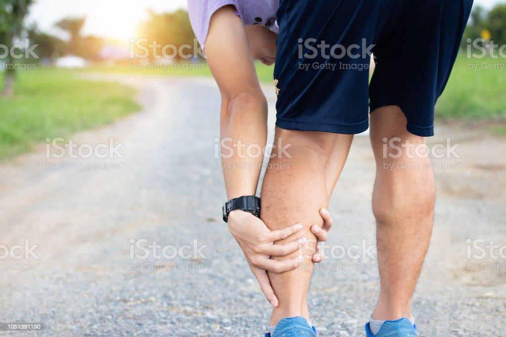 Male athlete runner muscle and ankle injury after jogging. Athlete man runner touching muscle in painful. Muscle and ankle injury concept. stock photo