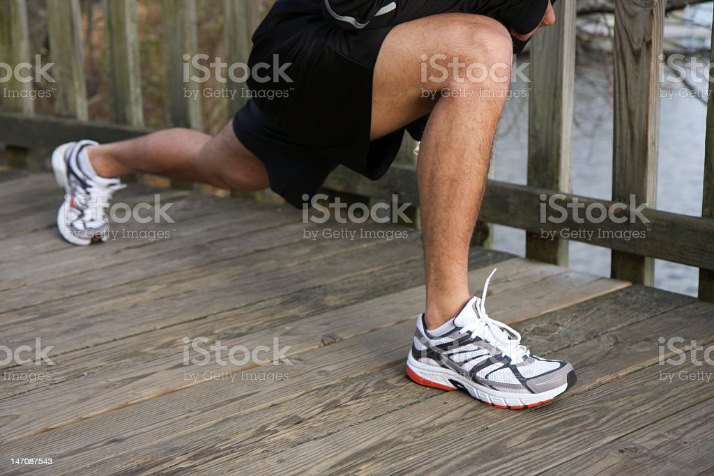 Male athlete runner stretching outside on dock stock photo