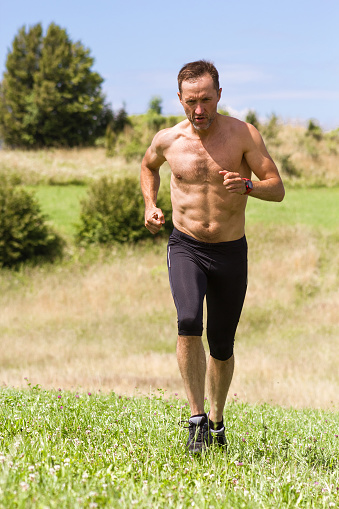 Male Athlete Runner With Naked Torso Training In Mountains