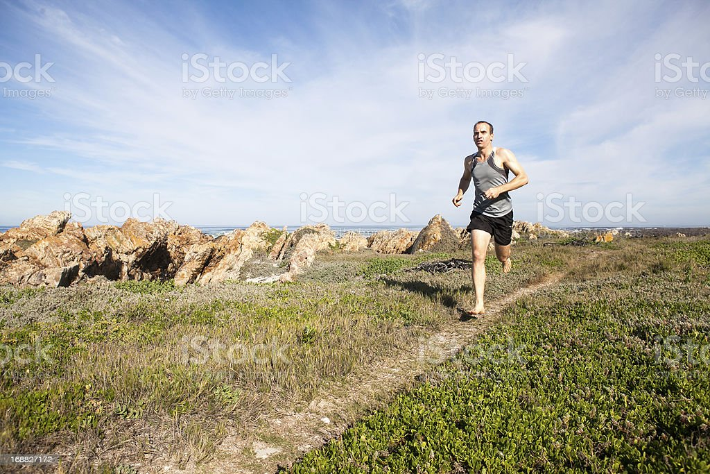 Male athlete running barefoot and fast on a walking trail stock photo
