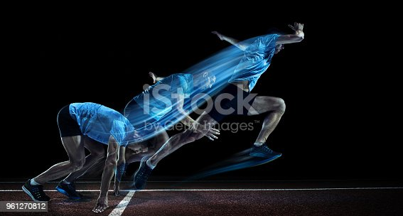 The young caucasian man running on running track on black background. Studio shot. Sport and healthy lifestyle concept with strobe effect.