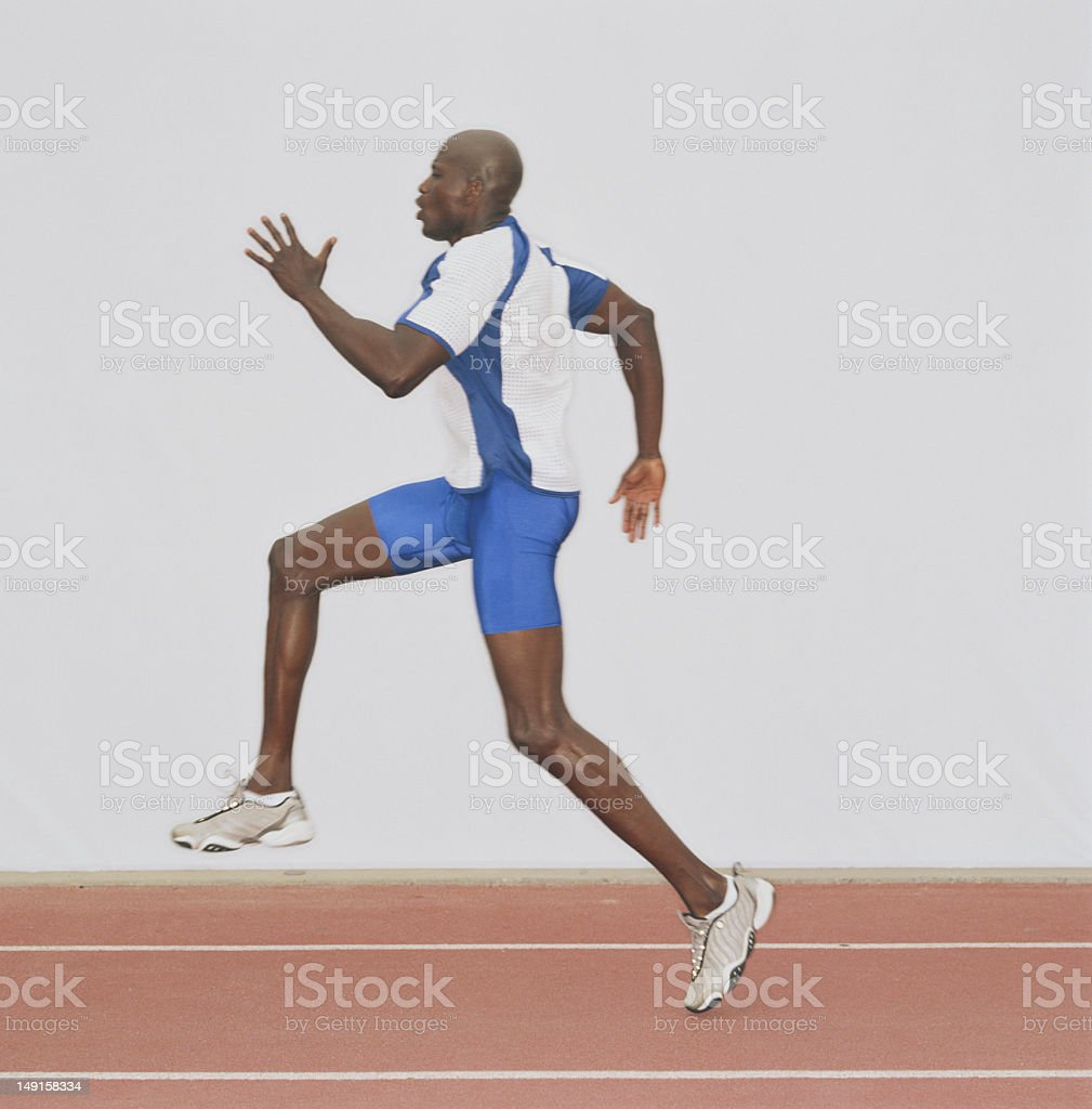 Male athlete running on track, side view royalty-free stock photo