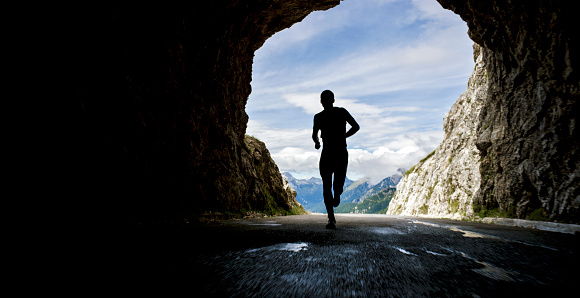 Male athlete running through tunnel in high mountain range on sunny day