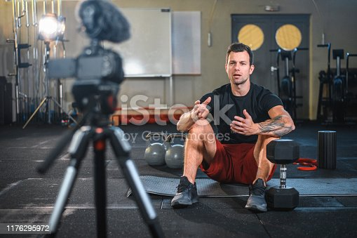 Caucasian male fitness instructor sitting on exercise mat at gym and making vlog explaining how to workout with kettlebells and dumbbells.