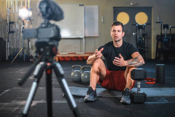 männlicher athlet sitzt auf übungsmatte und macht vlog im fitnessstudio - einzelner mann über 30 stock-fotos und bilder