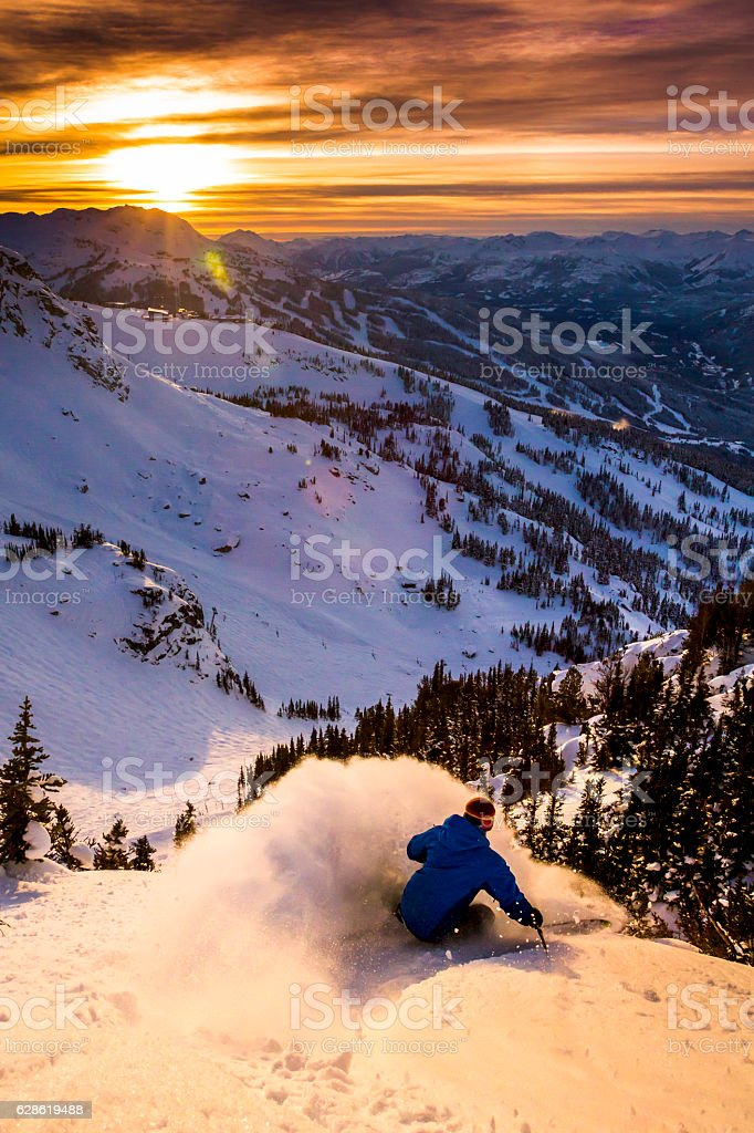 Male athlete skiing in deep powder during sunset. stock photo