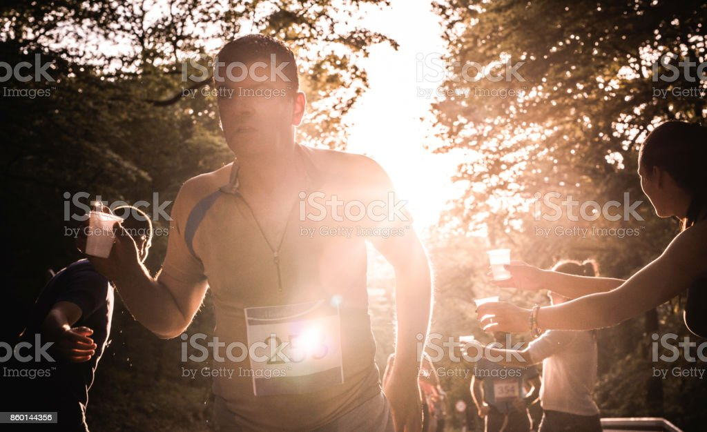 Male athlete taking water during marathon race in nature. stock photo