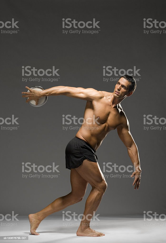 Male athlete throwing discus, studio shot royalty free stockfoto
