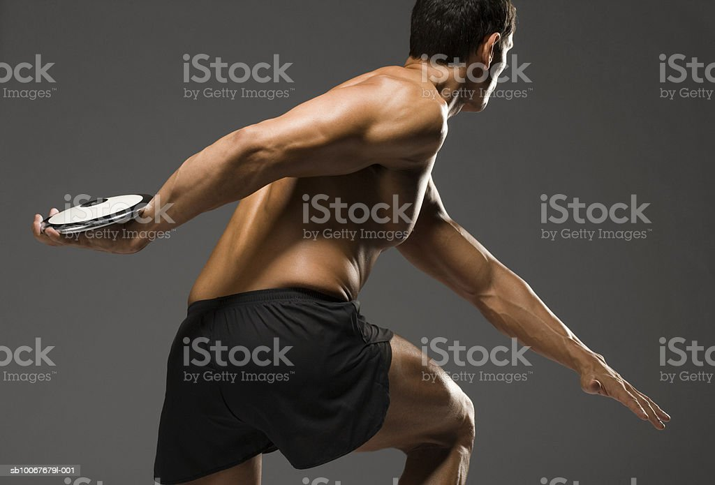 Male athlete throwing discus, studio shot royalty-free stock photo